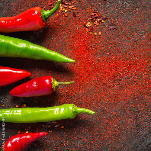 Fotobehang Hot chili peppers Red and green hot pepper and dry ground pepper on a dark background