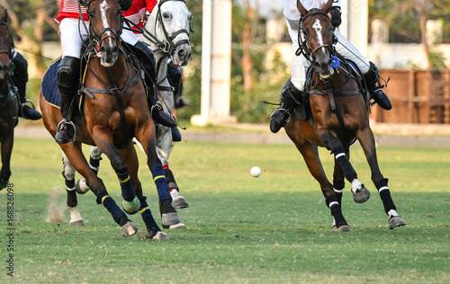 Ball is floating in the air during a polo match.