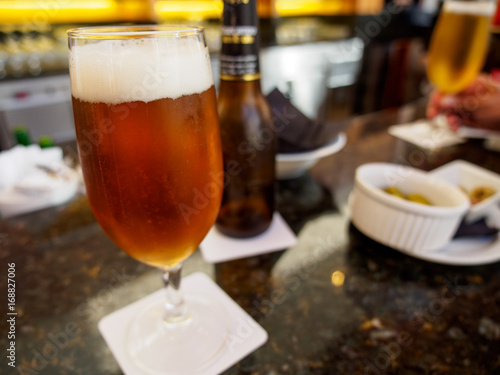 Close-up detail of an ale beer in a stemmed glass on a bar counter, with olives in ramekins as an appetizer, and a hand and glass in the background. Valencia, Spain. Travel and drinks concept.