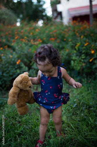 niña bebé juega con su oso de peluche en un parque lleno de flores Poster