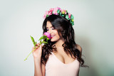 Happy Brunette Woman with Long Curly Hair and Spring Flowers having Fun on Banner Background