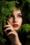 Lovely young woman with red lips posing on a background of thuja