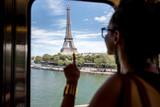 Young woman looking on the Eiffel tower through the train window in Paris. Woman is out of focus