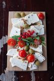 Deska serów z pomidorkami cherry, porzeczkami, oliwkami i orzechami