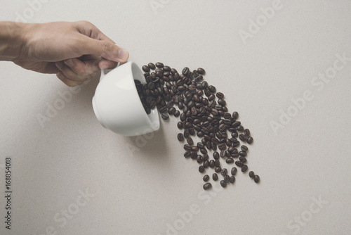 creative hand holding white coffee cup with coffee beans.