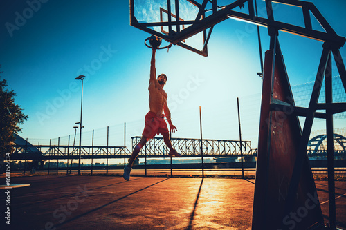 Street basketball athlete performing slam dunk on the court during the sunset