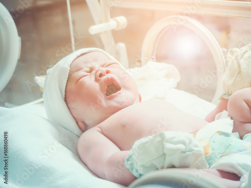 Newborn baby girl inside incubator in hospital post delivery room