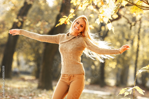 Beautiful blond hair woman dancing in the park on beautiful autumn day.Happiness.