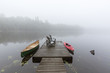 Canoe and kayak tied to a dock on a misty lake - Ontario, Canada