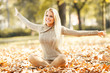 Beautiful blond hair woman sitting on leaves at the park on beautiful autumn day.