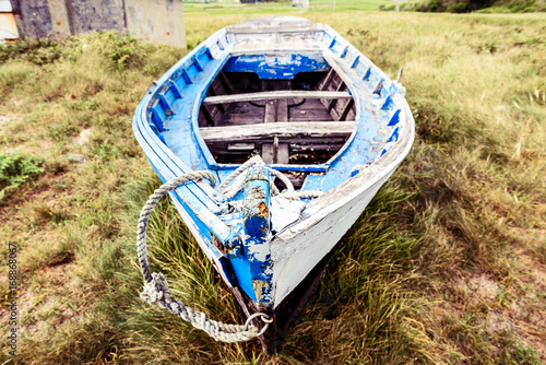 Papiers peints Naufrage Old abandoned wooden fishing boat stranded on land and grass.