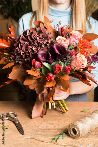 Female florist with bunch of autumn flowers