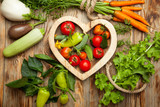 Vegetables in the heart on a rustic wooden background