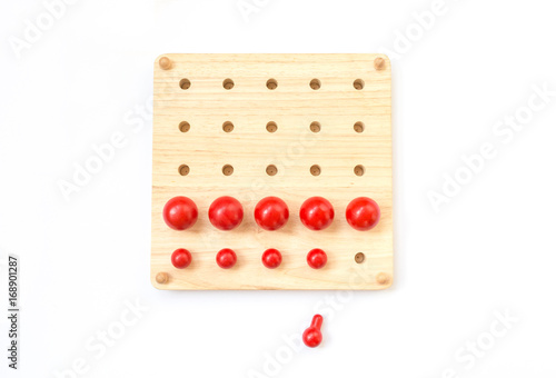 Red pegs board, wood beads on white background
