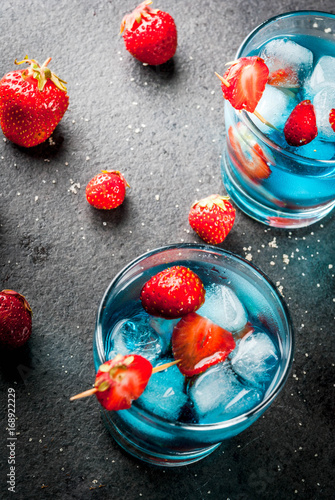 Summer refreshing cocktails, drinks. Strawberry berry colada with fresh berries and blue liqueur. On black stone table. Copy space