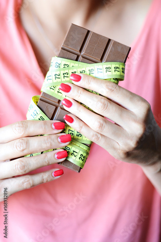 Young woman on diet holding one chocolate with yellow measurement tape wrapped around it
