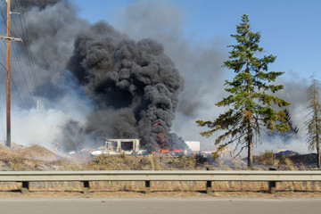 Billowing black smoke from burning tires at commercial site, caught in a brush fire.