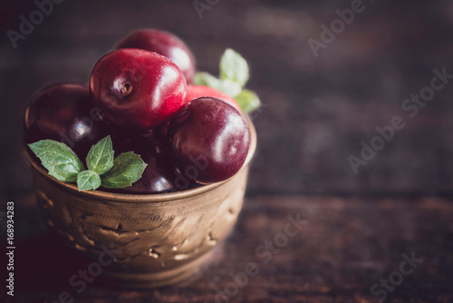 Fotobehang Kersen Group of cherries in the old metal cup on wooden background with blank space,selective focus