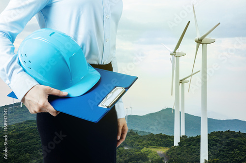 engineer holding helmet and wind power plant. renewable energy concept.