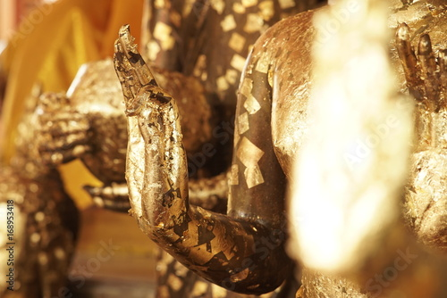 Antique Buddha Statues dated back to the 14th century covered in gold leaf adornment for good luck, good health, good virtue and prosperous at an ancient city of Phra Nakhon Si Ayutthaya, Thailand