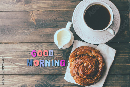 Cup of coffee and wood letters GOOD MORNING on wooden table background. Top view, copy space. Concept breakfast