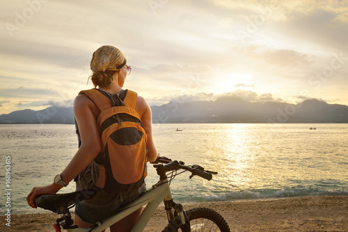 woman is traveling with a backpack on her bicycle.