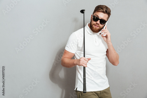 Calm golfer talking by the smartphone and holding club