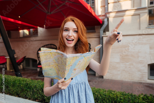 Excited pretty girl with long red hair holding map