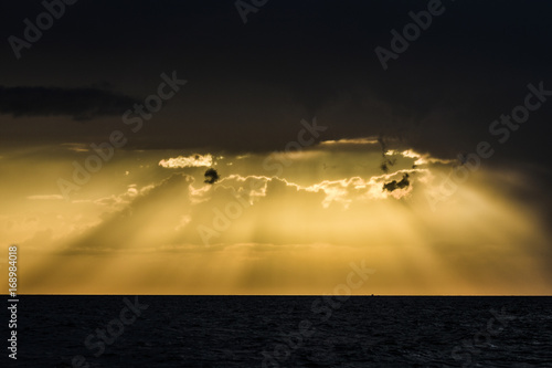 Yellow sunset with piercing light rays through the clouds.