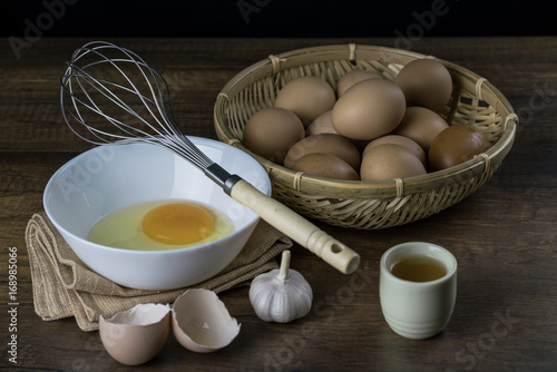 egg in the basket and whisk with garlic and Japanese green tea on wood background
