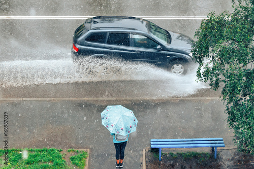 girl with umbrella standing under the rain at the bus stop