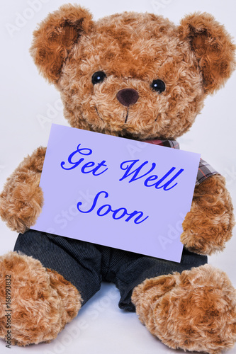 Teddy bear holding a purple sign that says Get Well Soon