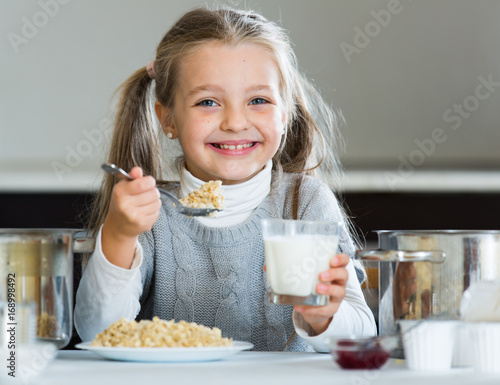 Cute little girl with milk and healthy oatmeal at  kitchen
