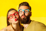 Freckled woman, and bearded man send air kissing at camera - 169000088
