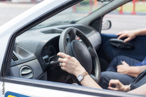 Plakat Senior woman learning to drive a car with a driving instructor