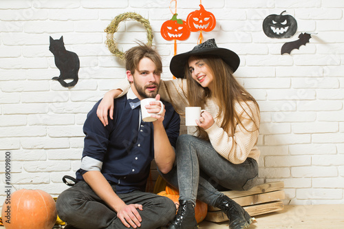 Halloween couple in love with cups drinking