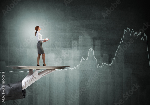 Attractive businesswoman on metal tray with red book in hands and graphs at background