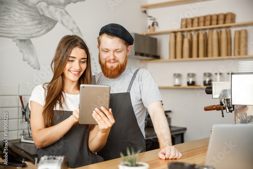 Coffee Business Concept - Satisfied and smile owners couple look on tablet orders online in modern coffee shop