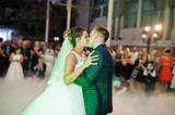 Beautiful wedding couple dancing their first dance in the huge hall with heavy smoke, different lights and people looking at them. - 169078009