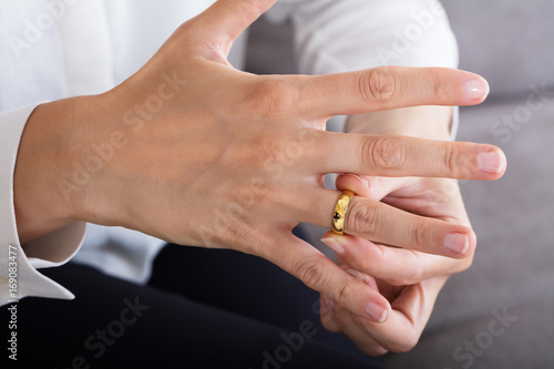 Woman Putting On A Shiny Gold Ring
