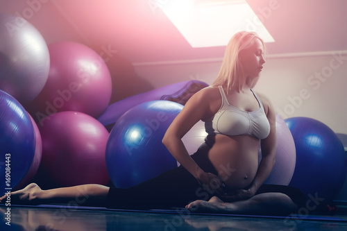 Mother with big belly in gym with fit balls