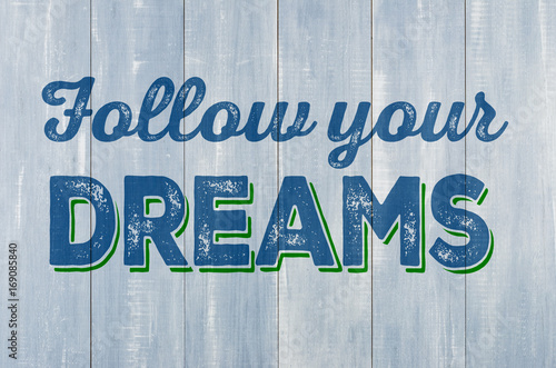 Blue wooden wall with the inscription Follow your dreams Poster