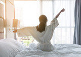 Easy lifestyle young Asian girl waking up in the morning taking a rest relaxing in hotel room for world lazy day concept - 169086447