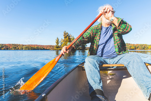 Senior man with canoe rowing on a sunny day
