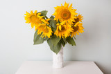 Bouquet of sunflowers in old ceramic vase against a white  wall.