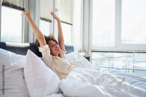 Young woman stretching in bed Poster