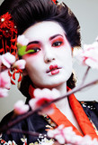 young pretty geisha in kimono with sakura and red decoration design on white background