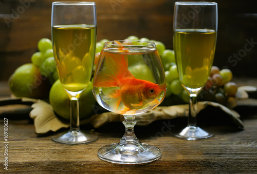 A fish in a glass against a background of grapes of wine glasses.