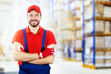 smiling young warehouse worker in red uniform. copy space - 169120401