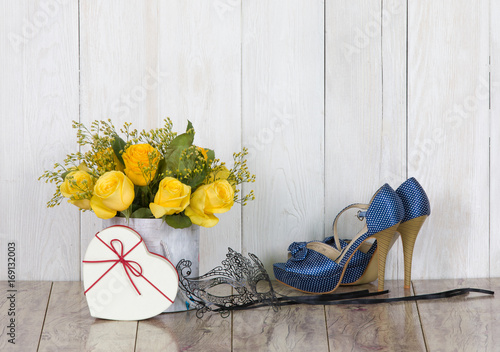 Yellow roses, women's shoes, theatrical mask